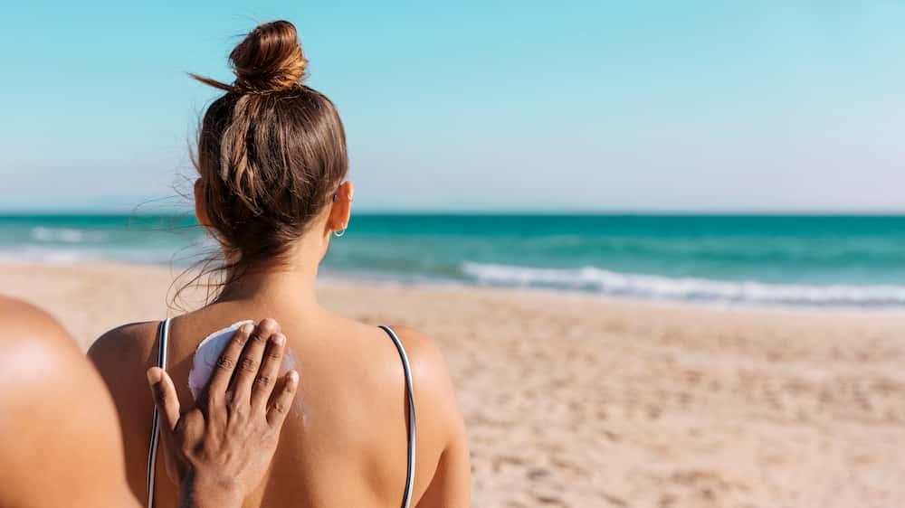 Biradam bir kadının sırtına güneş kremi dürüyor