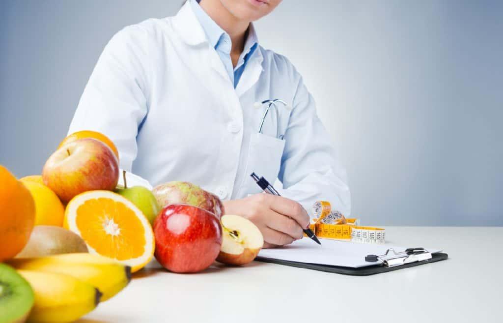 Masanın üzerinde meyveler ve diyet yazan bir kadın diyetisyen
