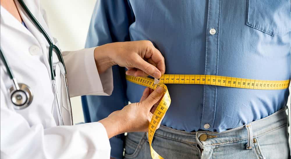 Diyetisyen bir hastanın bel çevresini ölçüyor