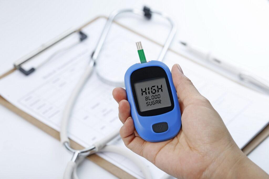 Kan şekerini ölçen bir kan şekeri ölçüm cihazı tutan el, arka planda bir stetoskop ve grafik dosyası